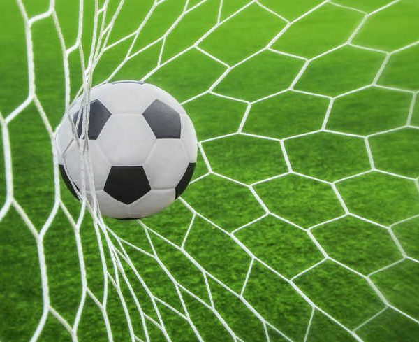soccer ball in goal with green background