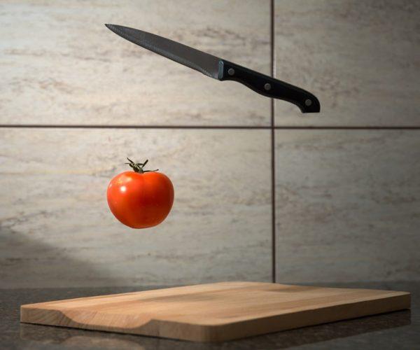 couteau et tomate au dessus planche a decouper